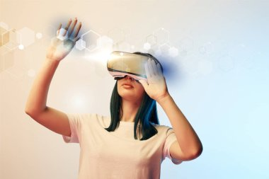 young woman in virtual reality headset pointing with hands at glowing abstract  illustration on beige and blue background