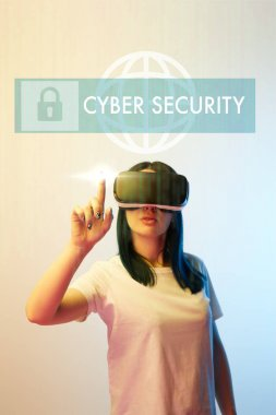 young woman in vr headset pointing with finger at cyber security illustration on beige and blue background