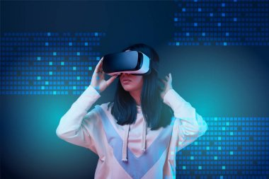 young woman in virtual reality headset among glowing cyber illustration on dark background