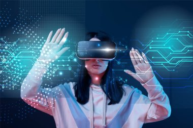 young woman in virtual reality headset gesturing among glowing cyber illustration on dark background