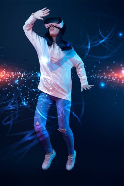 young woman in virtual reality headset flying in air among glowing data illustration on dark background