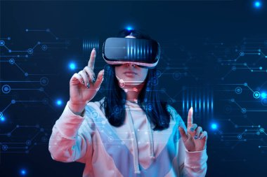 Young woman in virtual reality headset pointing with fingers at glowing cyber illustration on dark background stock vector