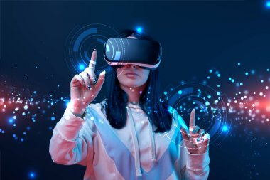 woman in virtual reality headset pointing with fingers at glowing cyber illustration on dark background
