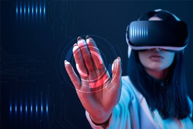 Selective focus of young woman in virtual reality headset pointing with hand at cyber illustration on dark background stock vector