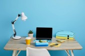 workplace with laptop and lunch box on wooden table on blue background, illustrative editorial