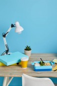 Fotografie workplace with lamp, folders and tasty lunch on wooden table on blue background