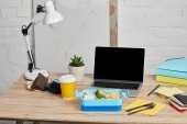 lunch box with rice, chicken and broccoli at workplace with laptop on wooden table on white background, illustrative editorial