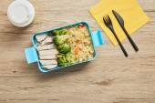 Top view of healthy lunch box with cooked chicken, broccoli, rice and coffee in plastic cup on wooden table