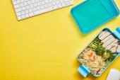 Fotografie Pohled na zdravé lahodné jídlo v plastikové krabici na oběd a počítačovou klávesnici na žlutém pozadí