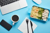 Top view of workplace with digital devices, cup of coffee and lunch box with rice, broccoli and chicken on blue background,illustrative editorial