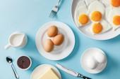 felülnézet a főtt és sült tojás, vaj, dzsem fehér lemezeken, tej, Villa, kanál és kés, kék háttér