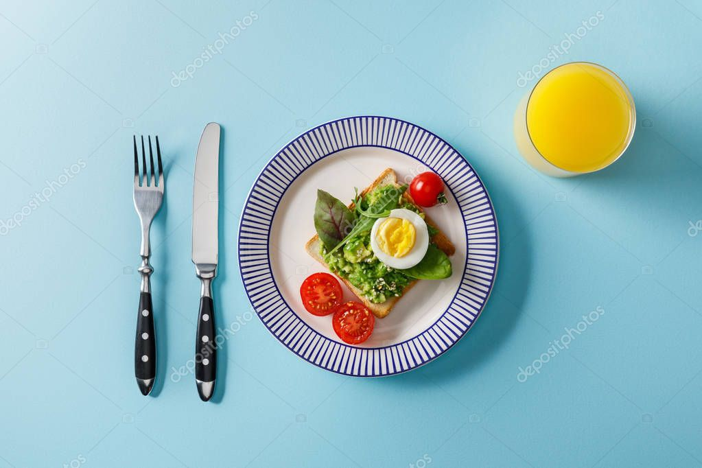 Top view of served breakfast, toast with guacamole and orange juice on blue background stock vector