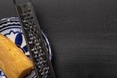 top view of sharp grater with cheese on ornate plate on black background