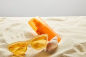 yellow stylish sunglasses and sunscreen in orange bottle on sand with seashell on grey background