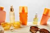 various sunscreen products in bottles on sand near fashionable sunglasses and seashells on grey background