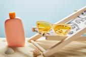 Fotografie krém na ochranu proti slunečnímu záření v písku blízko mušlí, žluté sluneční brýle a palubní židle na modrém pozadí