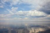 Nyugodt tó és világoskék ég, fehér felhők