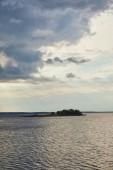 modré mraky na světle modrém nebi nad řekou s lesem na ostrově