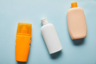 top view of sunscreen products in bottles on blue background