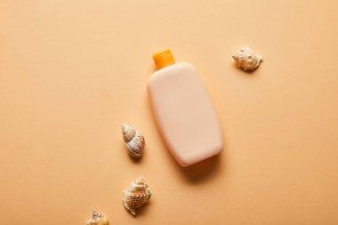 top view of sunscreen in bottle near seashells on beige background