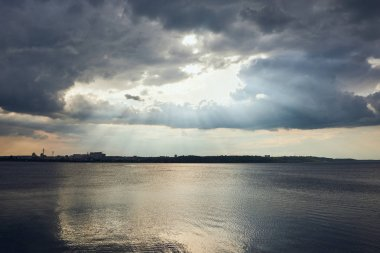 River coastline, overcast weather and clouds with sunlight