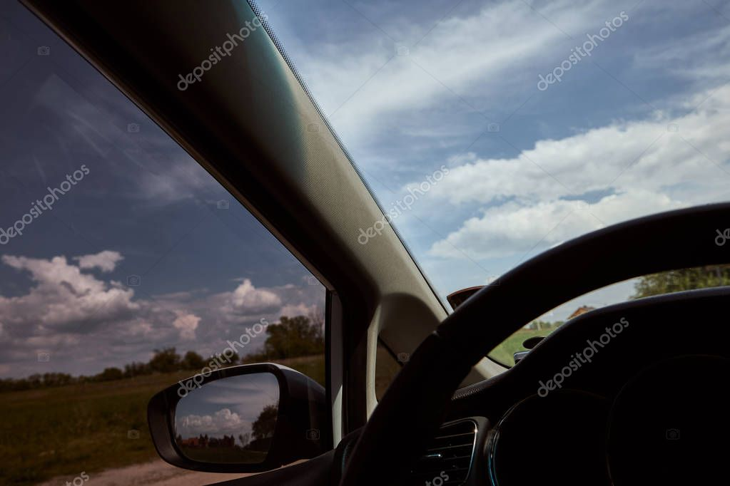Blue sky with white clouds, field and trees behind car window