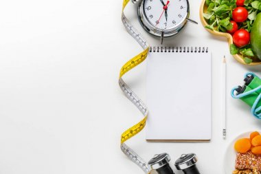 top view of sport equipment, measuring tape, alarm clock and diet food near empty notebook on white background