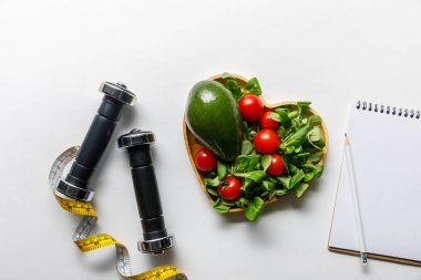 top view of vegetables in heart-shaped bowl, measuring tape, notebook and dumbbells on white background