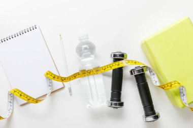 Top view of water in bottle, measuring tape, dumbbells and blank notebook with pencil near box on white background stock vector