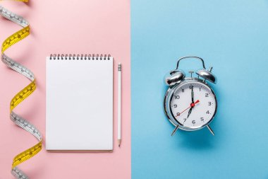 top view of measuring tape and blank notebook with pencil on blue and alarm clock on pink background