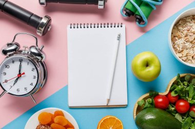 top view of empty notebook and pencil with delicious diet food and sport equipment on blue and pink background