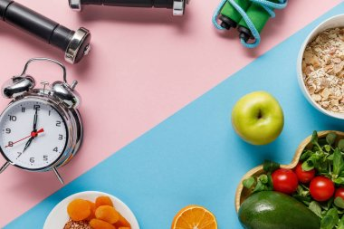 top view of delicious diet food and sport equipment with alarm clock on blue and pink background