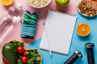 top view of empty notebook and pencil with delicious diet food, water and sport equipment on blue and pink background
