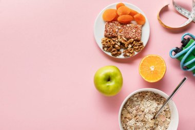 top view of fresh diet food, measuring tape, skipping rope on pink background with copy space