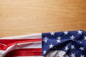 Photo top view of american flag on beige wooden surface with copy space