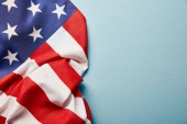 top view of crumpled american flag on blue background with copy space