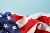 Photo close up view of american crumpled national flag on blue background with copy space