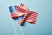 Photo top view of american flags on sticks on blue background