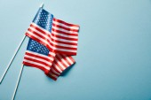 top view of national american flags on blue background with copy space