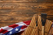 Photo top view of crumpled american flag and bbq equipment on wooden rustic table with copy space
