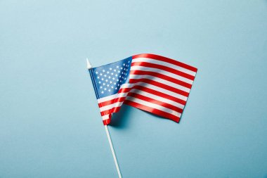 top view of american flag on stick on blue background