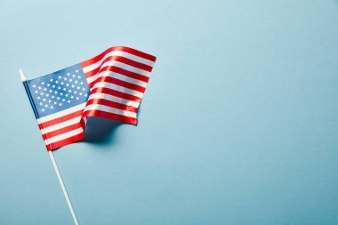 top view of usa flag on stick on blue background with copy space