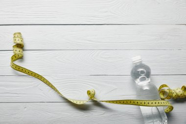 Top view of transparent bottle with water and yellow measuring tape on wooden white background with copy space stock vector