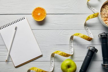 top view of measuring tape, breakfast cereal in bowl near apple, orange, notebook, dumbbells and pencil on wooden white background with copy space