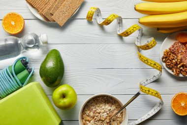 top view of diet food near measuring tape and sport equipment on wooden white background with copy space