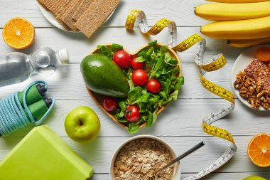 top view of measuring tape, cereal, fruits and vegetables in heart-shaped bowl and sport equipment on wooden white background