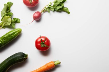 top view of raw fresh vegetables with green leaves on white background with copy space