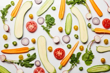 top view of fresh sliced tasty vegetables on white background