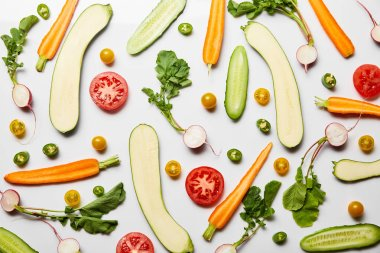top view of fresh sliced vegetables on white background