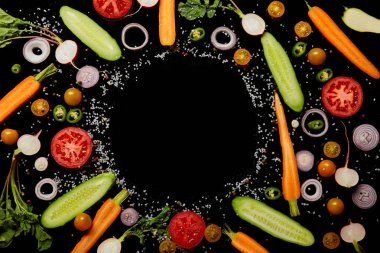 top view of fresh vegetable slices with salt with empty round frame isolated on black